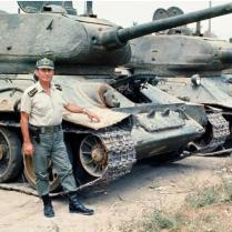A Turkish Soldier Posing In Front of a Greek Tank
