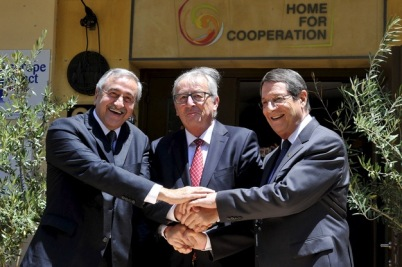 Greek Cypriot leader and Cyprus President Nicos Anastasiades shakes hands with European Commission President Jean-Claude Juncker and Turkish Cypriot leader Mustafa Akinci in Nicosia