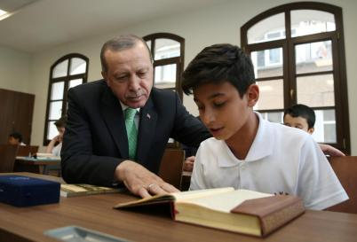 Turkish President Erdogan looks on as a student reads the Koran at the Recep Tayyip Erdogan Imam Hatip School in Istanbul